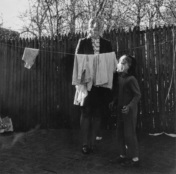 Black-and-white photograph of an adult and child in rubber masks standing behind a clothesline with a few garments