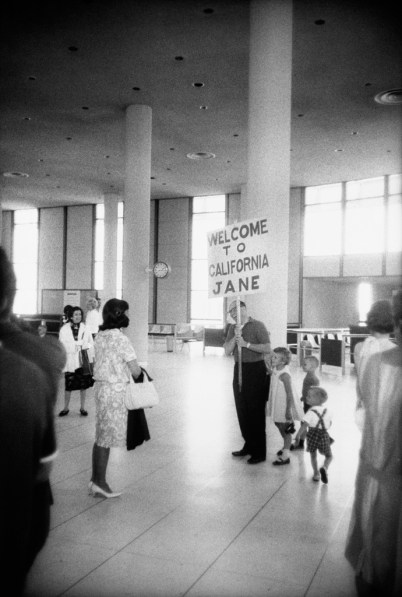 Black-and-white photograph of a man with three small children holding a sign reading WELCOME TO CALIFORNIA JANE greeting an approaching woman