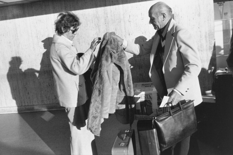 Black-and-white photograph of an older man passing a fur coat to a woman over their suitcases