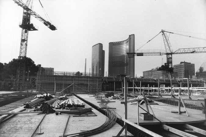 Black-and-white photograph of two cranes overlooking an empty construction site