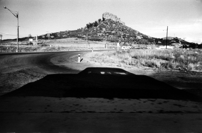 Black-and-white photograph of a roadside overlooking a rocky outcrop on a hill