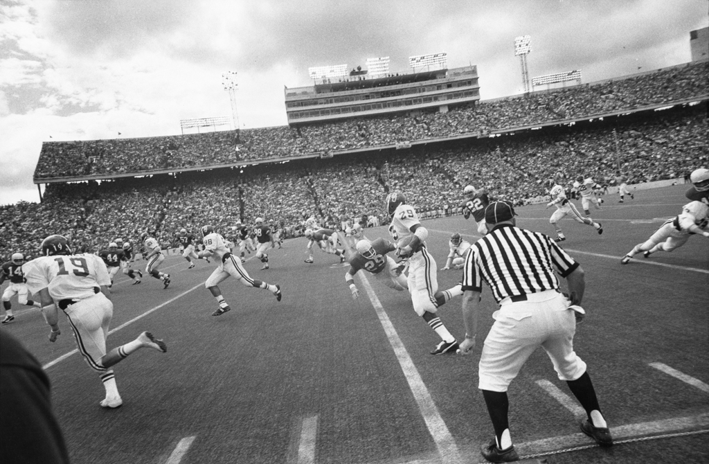 Black-and-white photograph of an American football game in progress against the backdrop of a full stadium