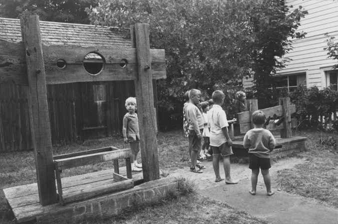 Black-and-white photograph of a group of children inspecting empty wooden stocks