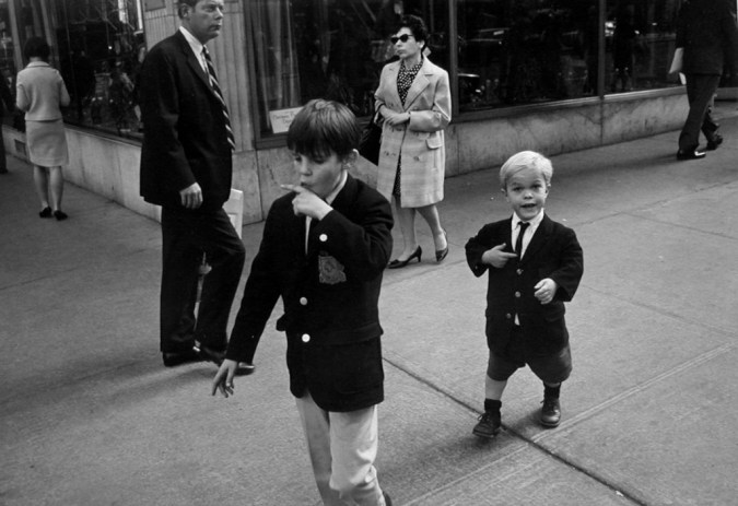 Black-and-white photograph of two boys in school uniforms passing through a street corner