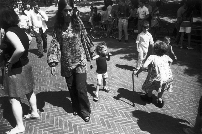 Black-and-white photograph of a woman walking down a brick pavement holding a young girl's hand