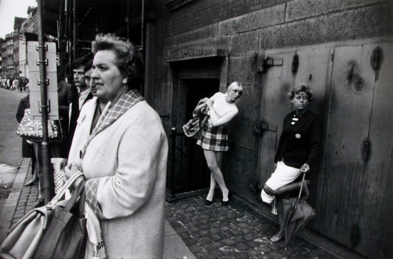 Black-and-white photograph of two women against an exterior building wall looking down a street