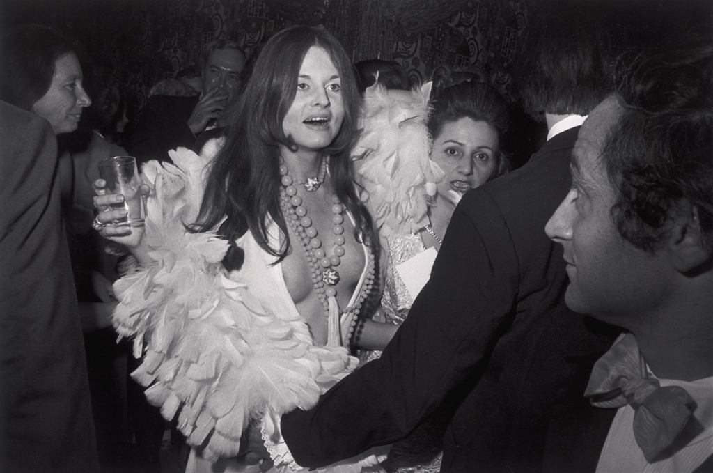 Black-and-white photograph of a woman in a low v-neck top with feathers and beaded necklaces holding a glass amidst a crowd of people