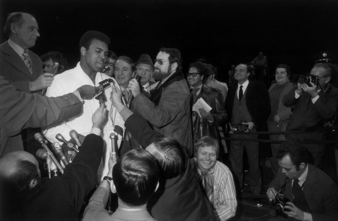 Black-and-white photograph of a boxer being interviewed by reporters with microphones and cameras