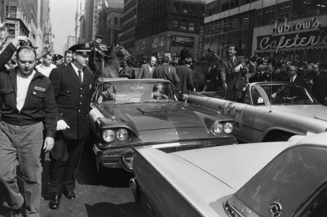 Black-and-white photograph of a parade of convertible cars moving down a crowded avenue