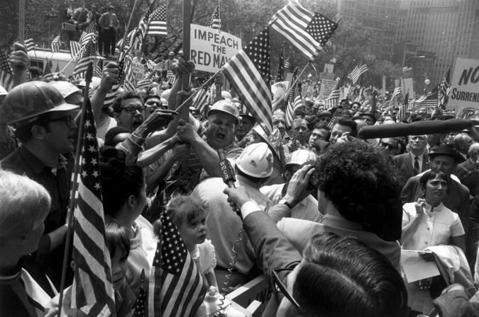 Black-and-white photograph of a crowd of people in hardhats holding signs and American flags being interviewed by a reporter with a microphone