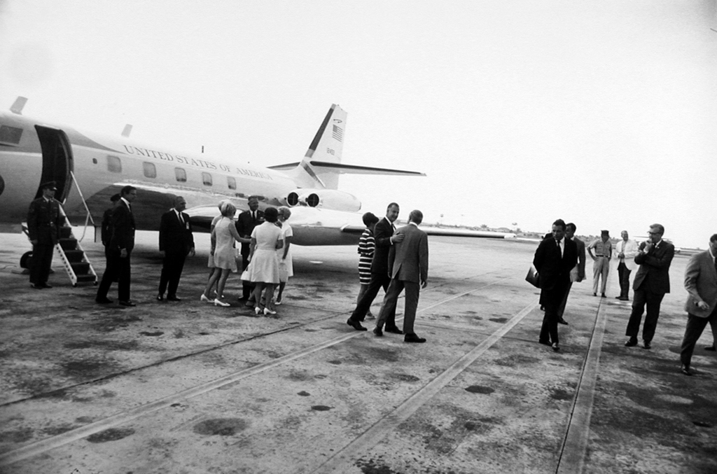 Black-and-white photograph of a small group disembarking from a United States jet on the runway