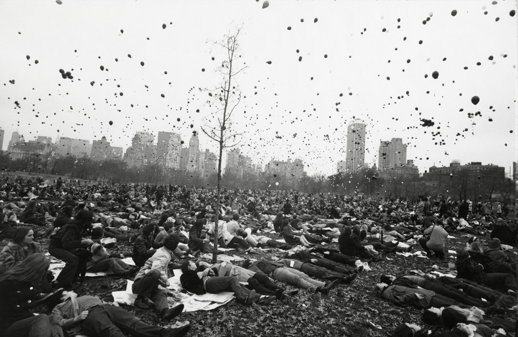 Black-and-white photograph of people sitting on blankets in a meadow under a sky filled with helium balloons