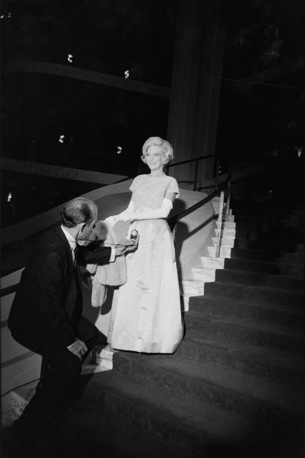 Black-and-white photograph of a woman in a pale gown descending a curving staircase towards a man in a suit