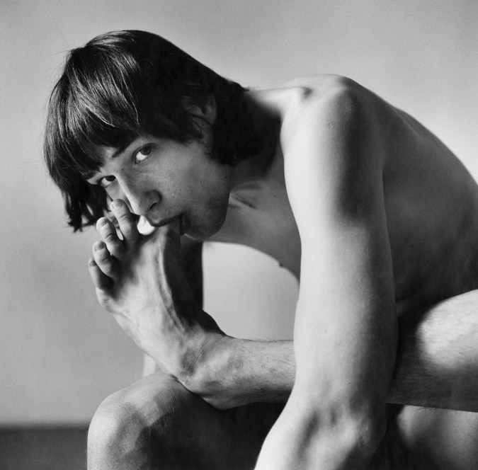 Black-and-white photograph of a seated nude man leaning forward to suck his big toe