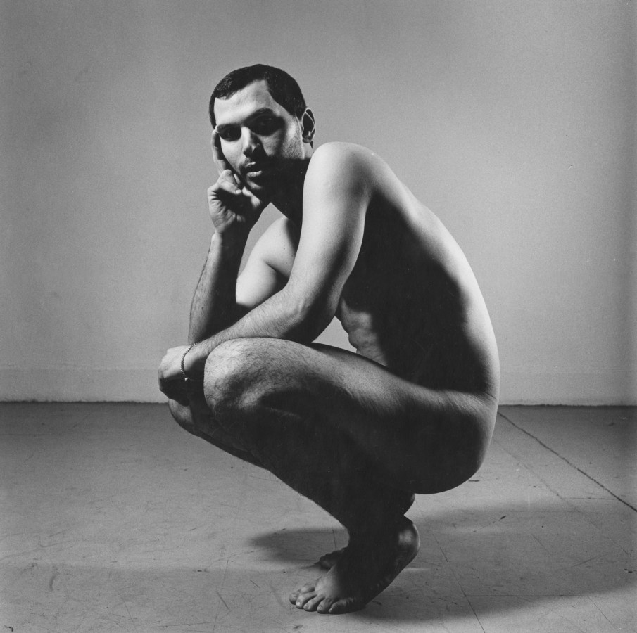 Black-and-white photograph of a crouching nude man with his cheek on one hand