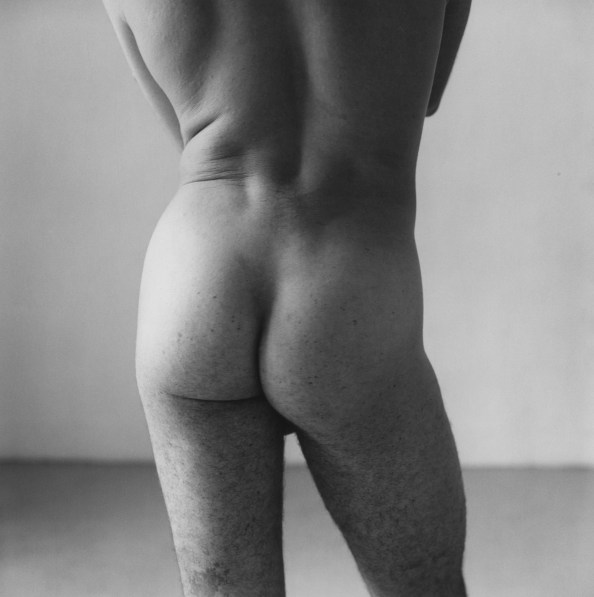Black-and-white photograph of a nude person's torso and buttocks