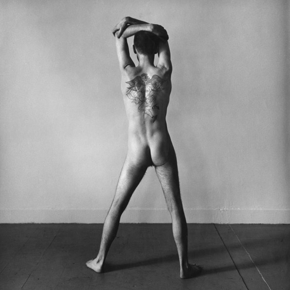Black-and-white photograph of a standing nude man with his tattooed back to the viewer and his arms above his head