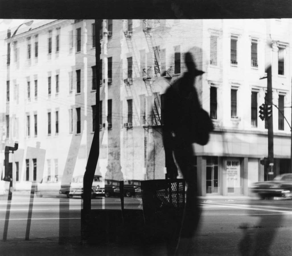 Black-and-white multiple-exposure photograph of a person's reflection against a city street