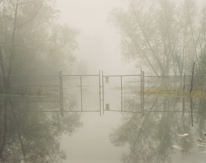 Color photograph of a chain-link fence and ajar gate in standing water through a gray-green haze