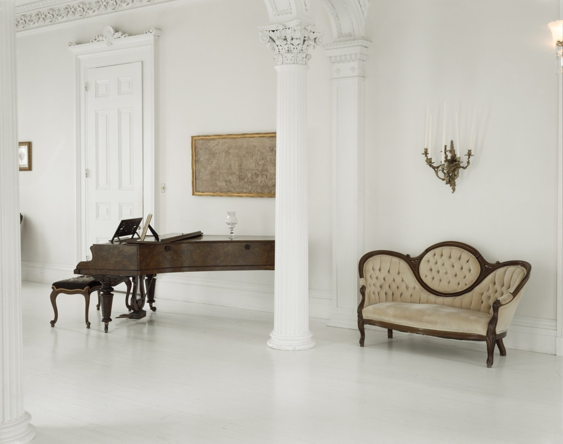 Color photograph of a white room with Neo-Classical detailing containing a beige sofa and dark wooden grand piano