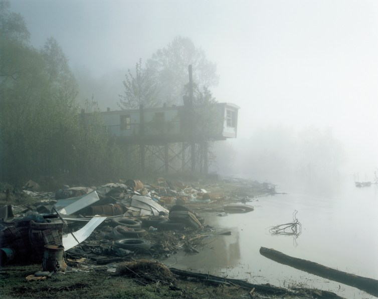 Color photograph of a decrepit trailer home on stilts standing above a shore filled with trash