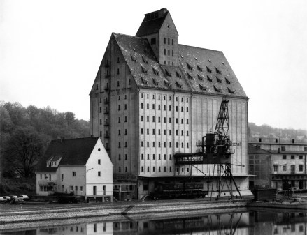 Black and white photograph of a large industrial building alongside a canal