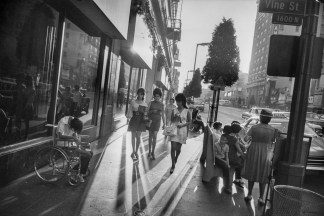 Black-and-white photograph of three women walking down a city sidewalk between a person in a wheelchair and a crowded bench
