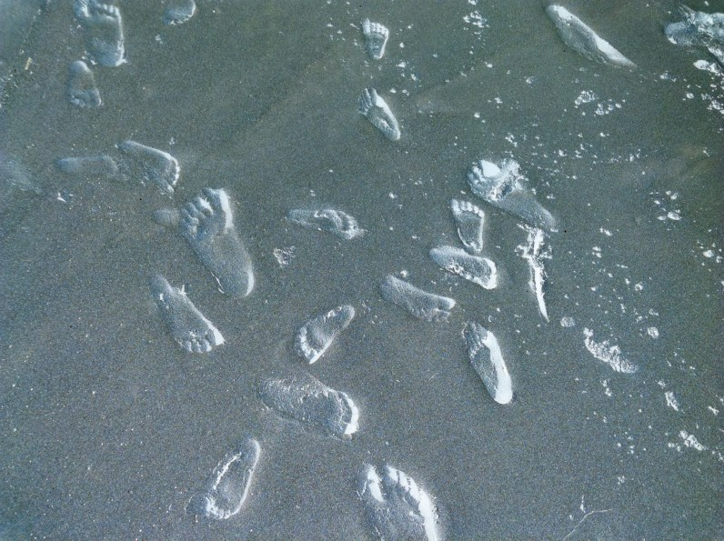 Inverted color photograph of shallow footprints in sand