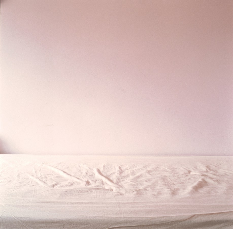 Color photograph of an unmade bed in front of a pink wall.