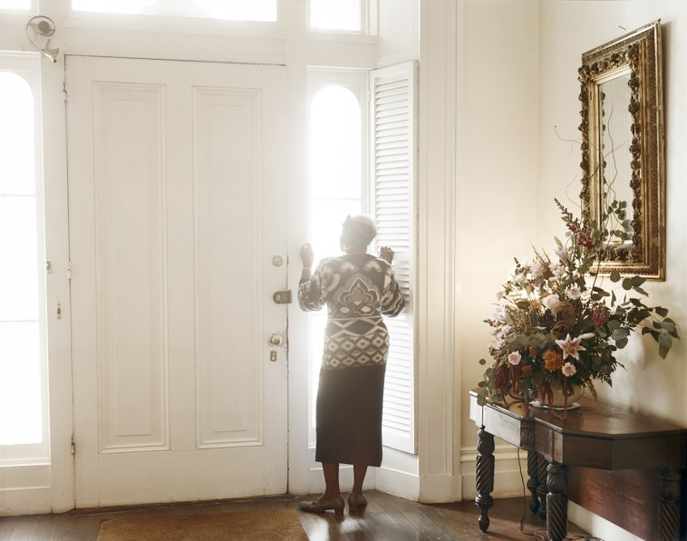 Color photograph of a woman peering through a light-filled window in a foyer