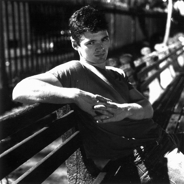 Black and white photograph of a young man reclining on a park bench