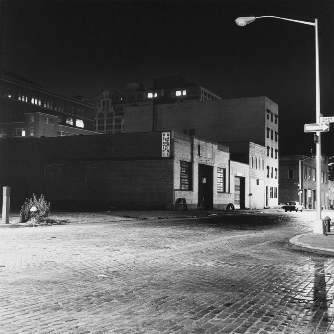 Black and white photograph of an empty street at night