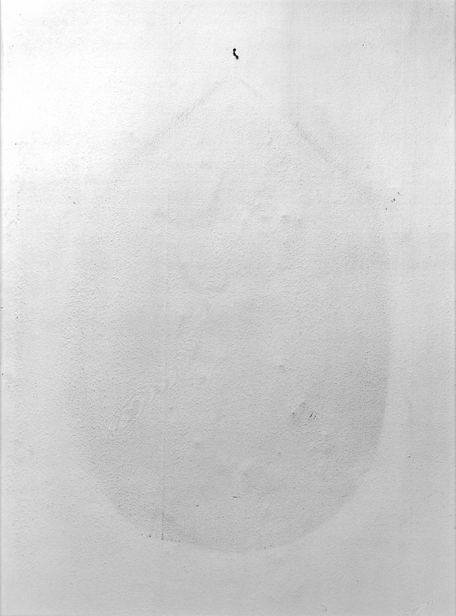 Black and white photograph of a blank wall with an teardrop shaped imprint underneath a lone nail