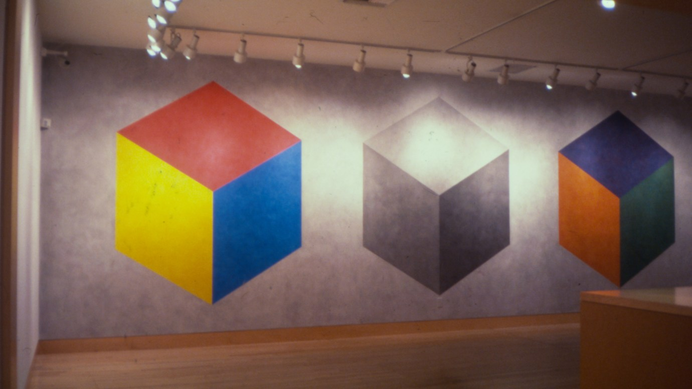 Installation photograph of a wall drawing of three cubes with faces of different colors on a grey background