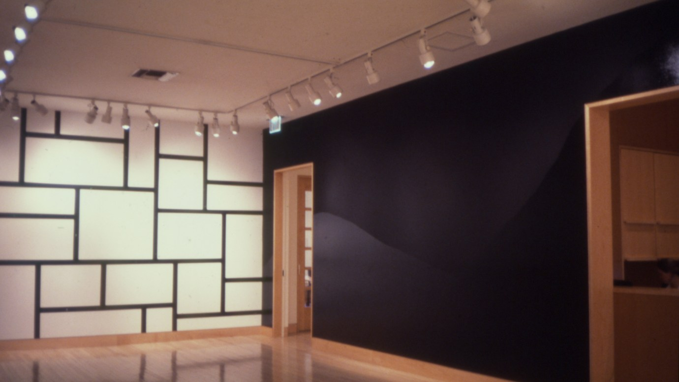 Installation photograph of a wall drawing of irregular black rectangles on a white wall