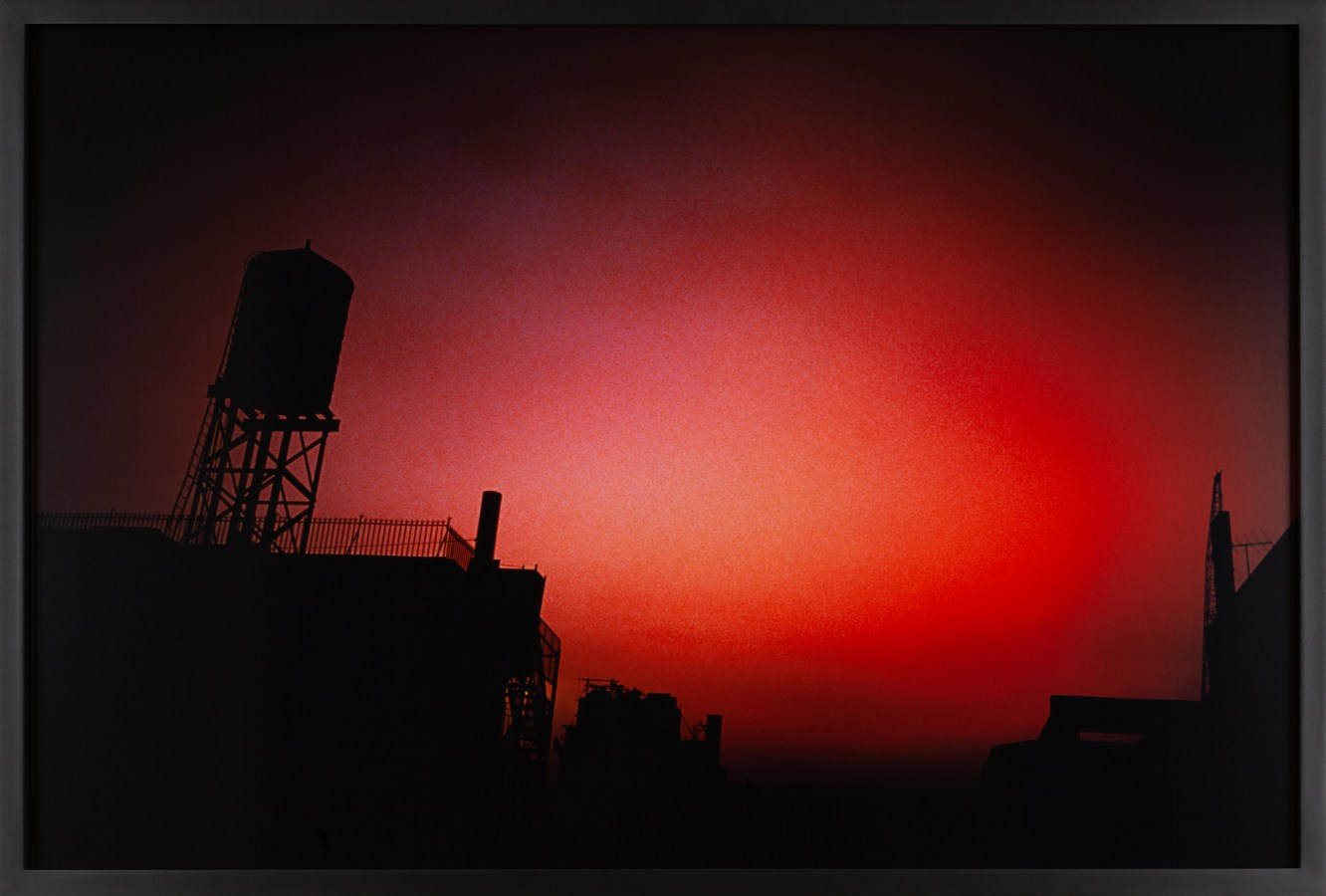 Color photograph of an overcast night sky with a red glow above city buildings and a rooftop watertower