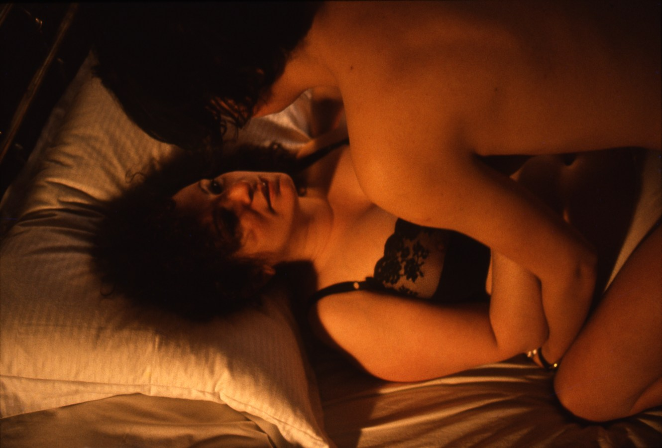 Color photograph of a woman lying in bed looking up from beneath her partner