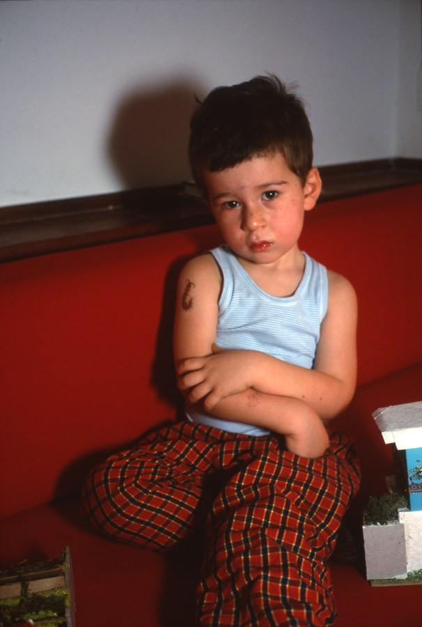 Color photograph of a seated young boy with an insect tattoo on one arm