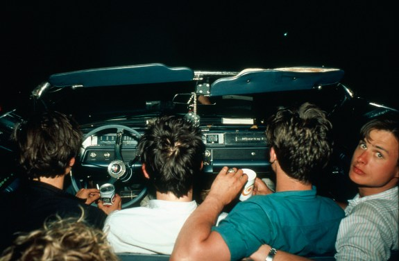 Color photograph from behind of four young men in the front seat of a convertible car with one looking back over his shoulder at the viewer