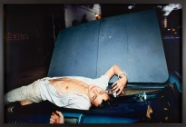 Color photograph of a young man with an open white shirt lying on the windshield of a blue car