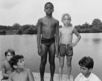 Black and white photograph of two boys in swimsuits standing on a concrete ledge above a lake with three others seated beneath them