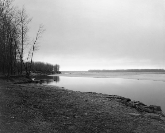 A black and white photograph of a river bank with leafless trees at the right edge of photograph and an overcast sky.