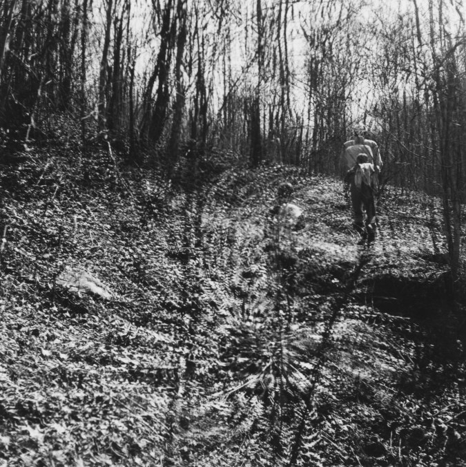 Black and white photograph of two figures making their way up a forested hill