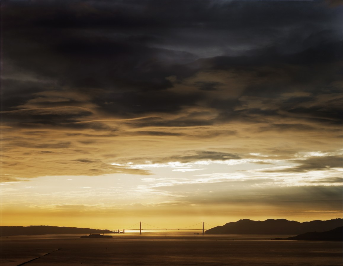 Color photograph of a bridge spanning a bay under a clearing of golden light through dark clouds