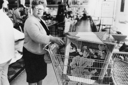 Black and white photograph of a woman with several framed paintings in a shopping cart