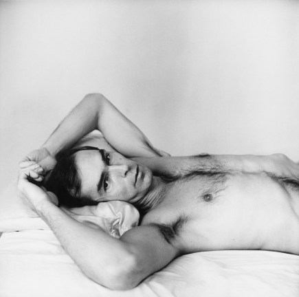Black-and-white photograph of a shirtless dark-haired man reclining with his hands in his hair