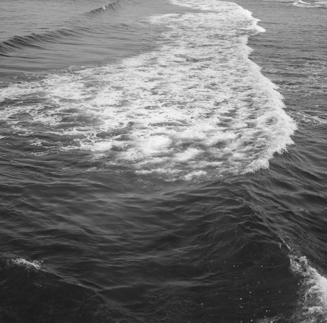 Black-and-white photograph of a wave moving from left to right and the trail of white water following it