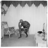 Black and white photograph of a man flexing his arm muscles seated a living room