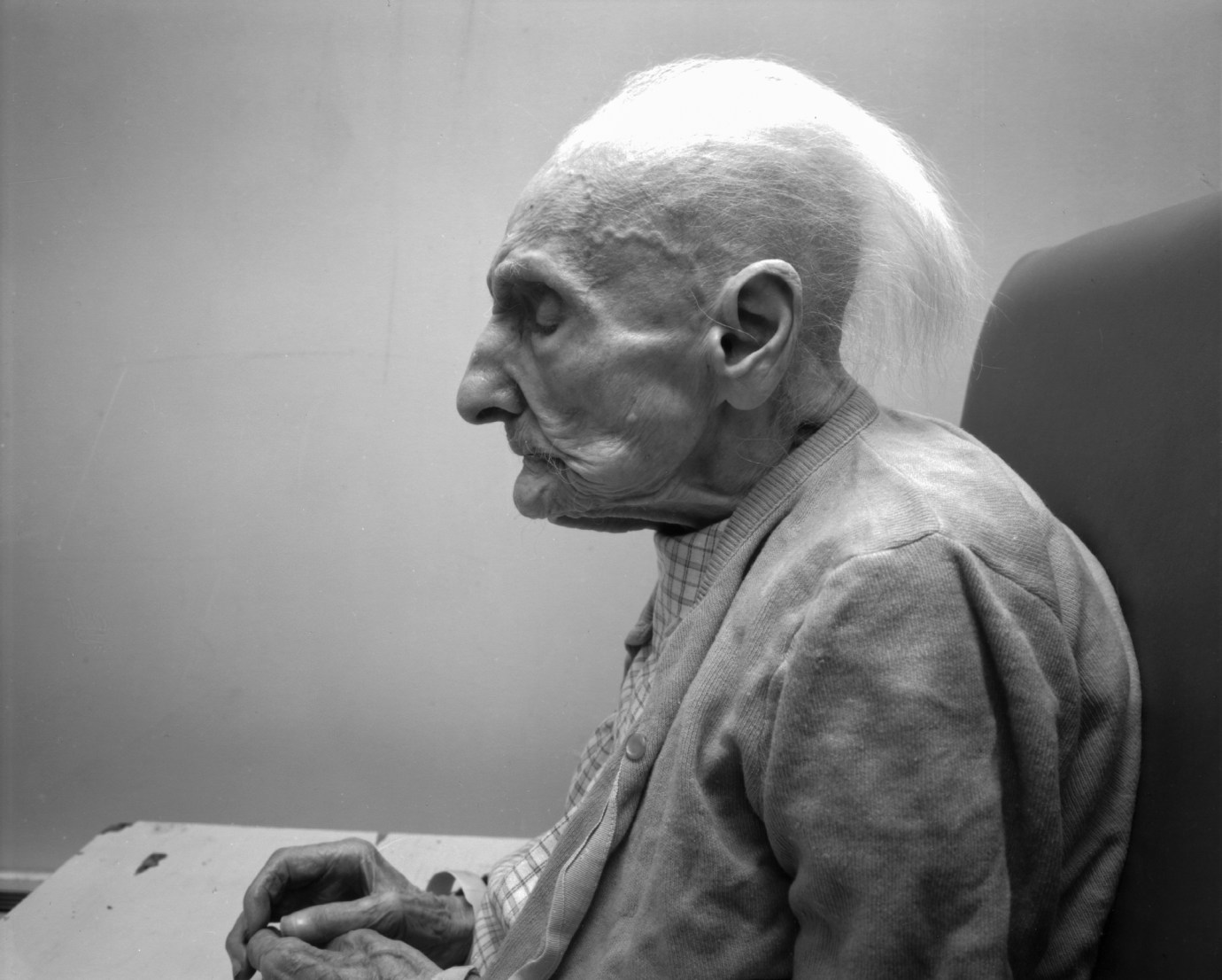 Black and white photograph of the profile of an elderly person seated with their eyes closed