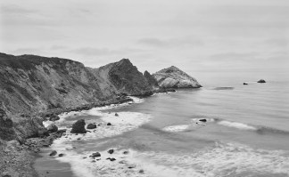 Black-and-white photograph of a cape curving around a bay with waves crashing on a rocky shore
